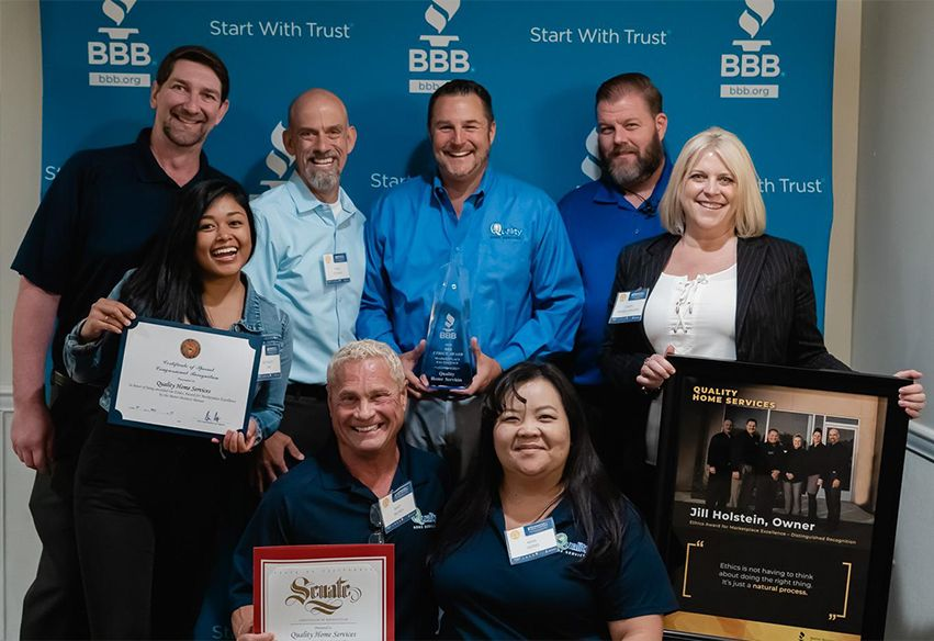 Quality Home Services staff with BBB award